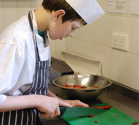 Catering student Michael Langley preparing food  for the Come Dine With Us event
