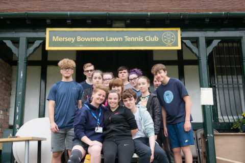 Group of volunteers in from of the Tennis Club they helped to renovate