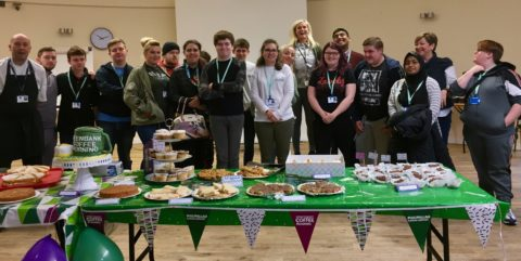 staff and students with an array of cakes on a table.