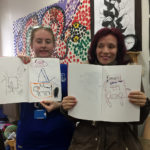 Two students standing with their art work