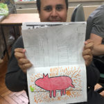 student showing his art work