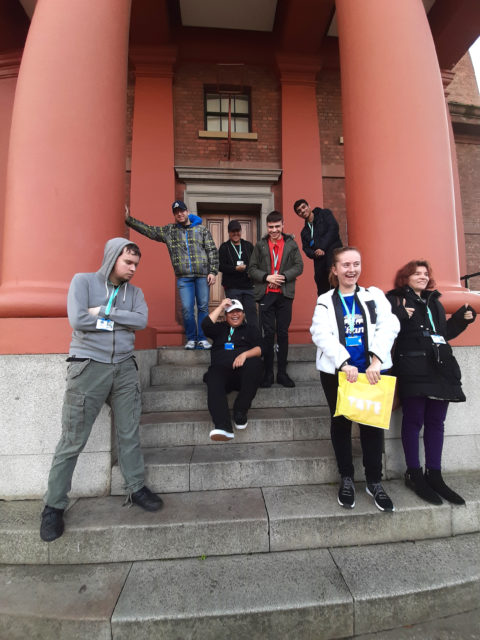Group of students standing and sitting on steps