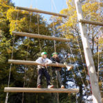 Two students climbing on a wide log ladder