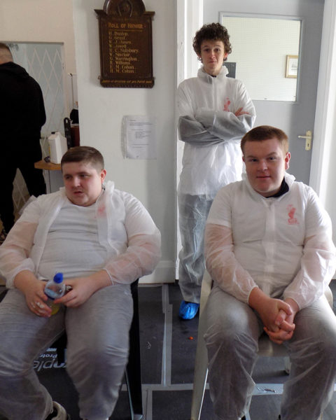 Three male students having a well earned break from their volunteering