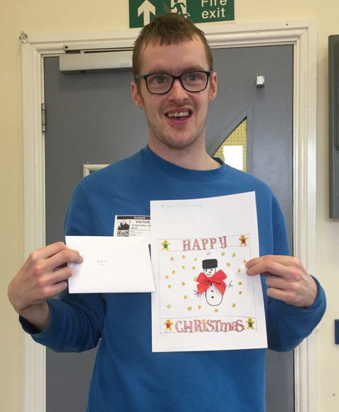 Student holding up their Christmas Card design