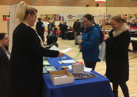 Students and parents talking to stall holders in a large sports hall