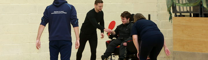Disability Sport Coaching and Development Foundation Degree students in the sports hall learning how to adapt sports for power wheelchair users