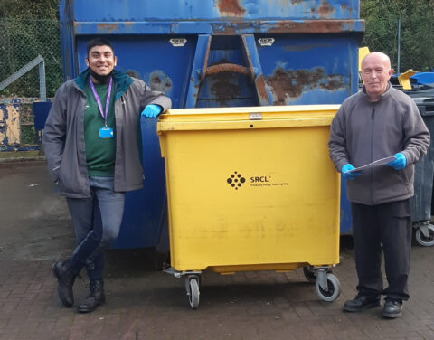 Supported intern Ifti leaning on a large yellow bin set against a larger refuse area with his work mentor on the right