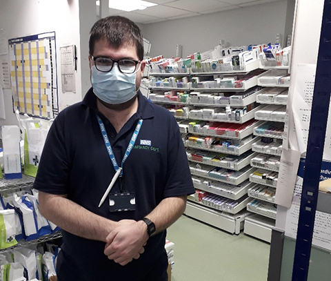 Young man looking at camera wearing a face mask standing in a pharmacy