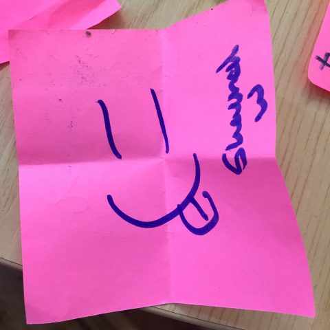 Smiley face drawing on a post-it note