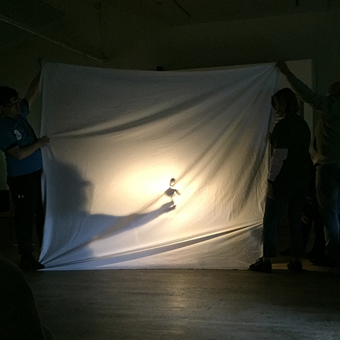 White sheet with light behind and shadow puppets